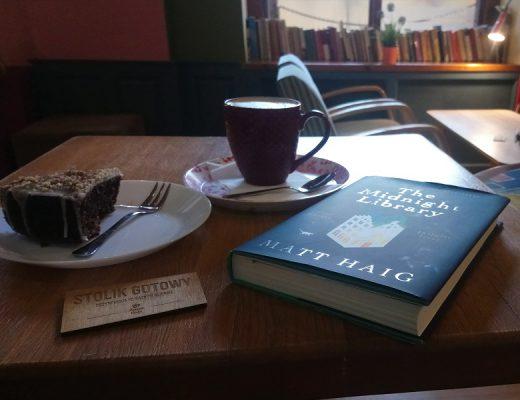 Stolik w kawiarni, kawa, ciasto i książka, w tle książki na parapecie