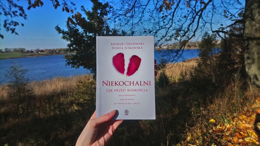 """Zdjęcie książki """"Niekochalni"""" na tle jeziora i drzew"""