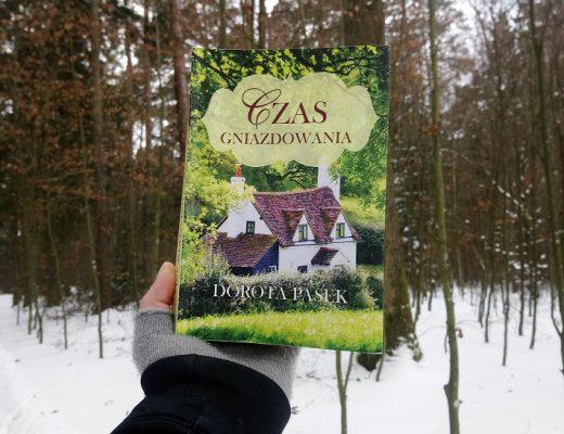 """Książka """"Czas gniazdowania"""" na tle zimowego lasu"""